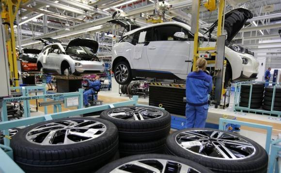 A worker mounts a tyre at the serial production BMW i3 electric car in the BMW factory in Leipzig