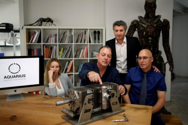 Shaul Yaakoby (R), CTO and Inventor, Gal Fridman (C), Chief Marketing Officer, Maya Gonik (L), Head of Business Development and Ariel Gorfung (standing), Chief Executive Officer from Israeli start-up Aquarius Engines pose for a picture next to a prototype of their combustion engine at their offices in Rosh Ha'ayin, Israel May 16, 2016. REUTERS/Amir Cohen